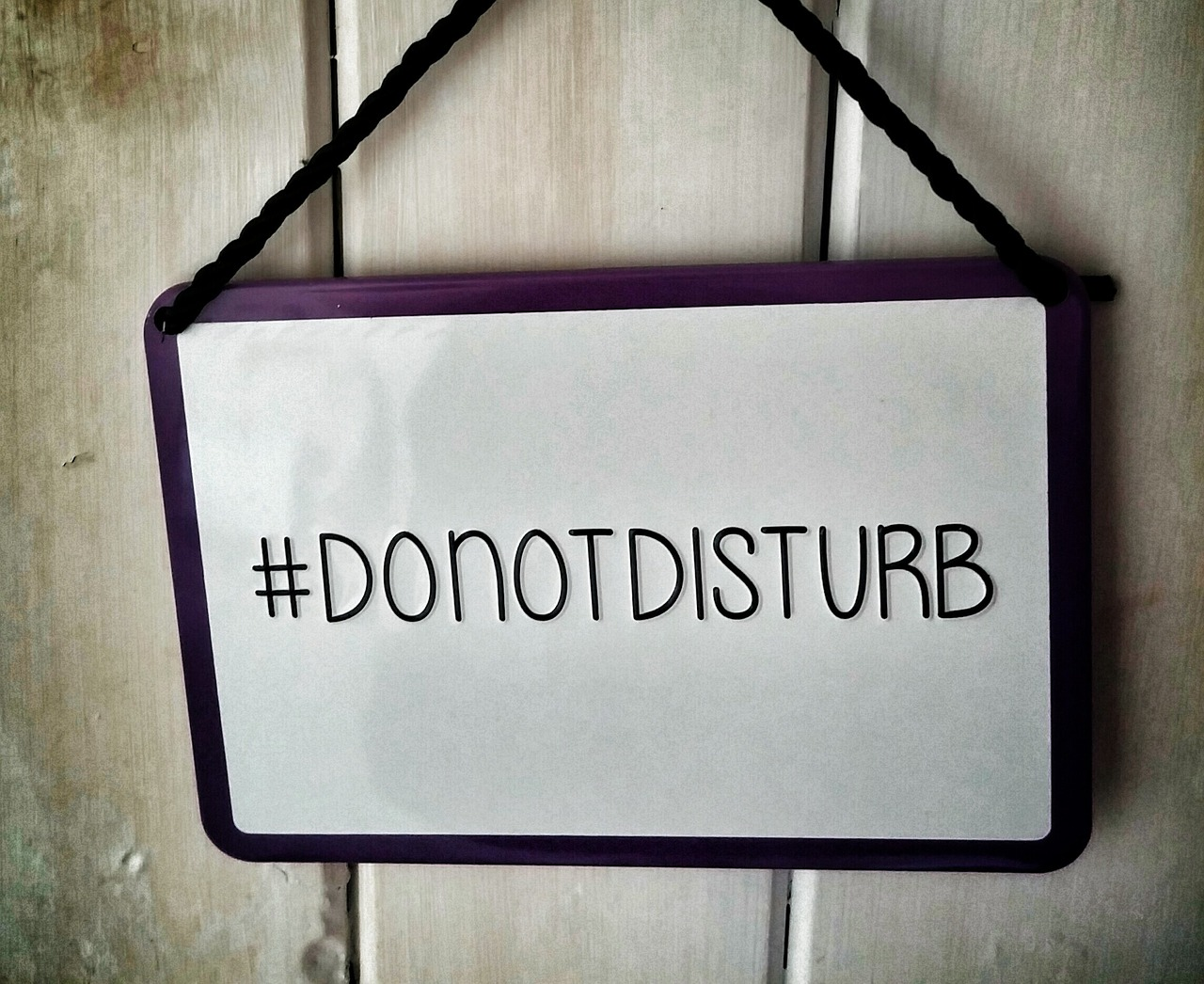 A white sign with a black border against a wooden wall. The sign reads in black letters #DONOTDISTURB